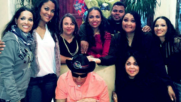 Image of Asaad Amin Ali with his father Muhammad Ali and with his sisters Laila, Maryum, Jamillah, Rasheda, Hana, Khaliah, and Miya Ali.