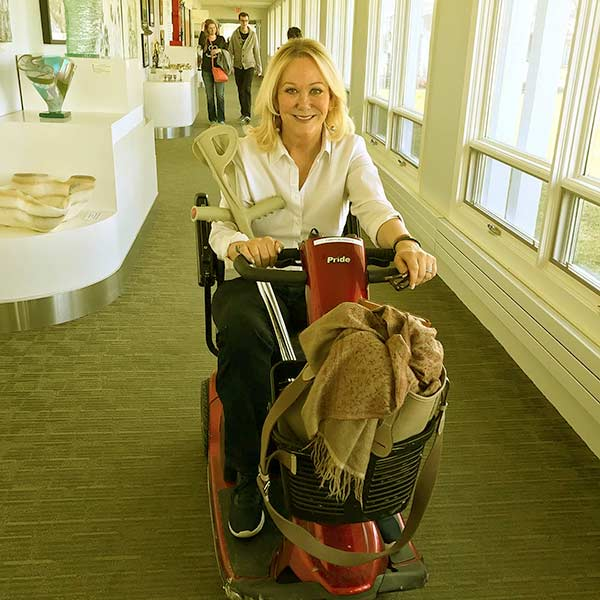 Image of Caption: Nina Griscom riding an electric scooter with crutches in-hand