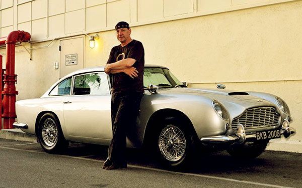 Image of Caption: Drummer, Neil Peart with his luxurious car Ashton Martin DBS